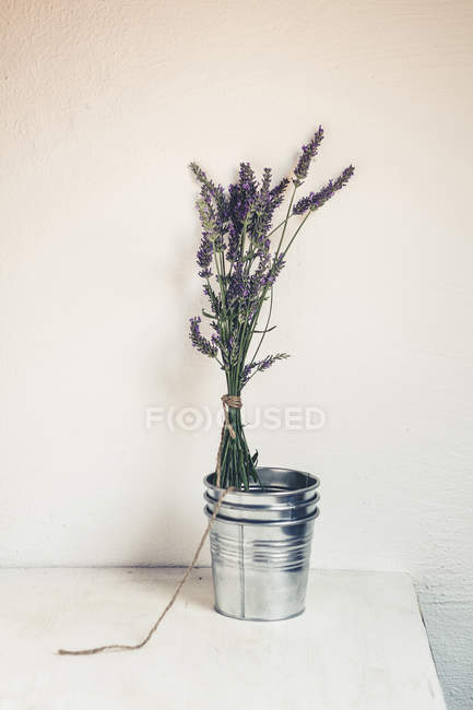 Bunch of lavender standing in zinc bucket in front of wall — Stock Photo