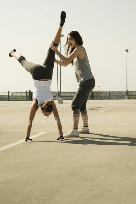 Jovem praticando suporte de mão assistido por um amigo — Fotografia de Stock
