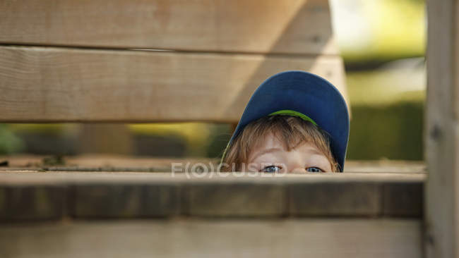 Gros plan du petit garçon caché à l'aire de jeux — Photo de stock
