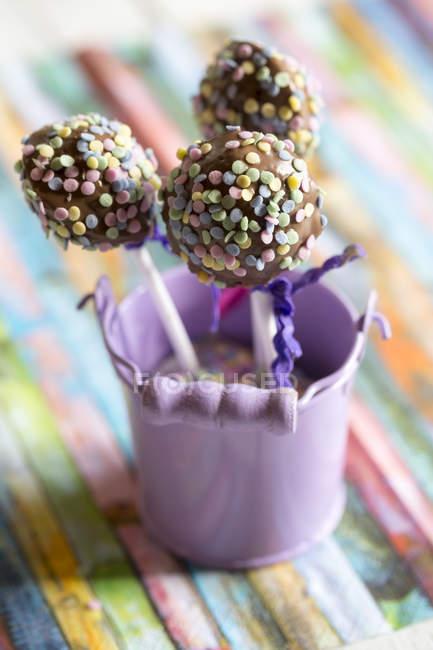 Cubo con tres cake pops en colores tierra - foto de stock