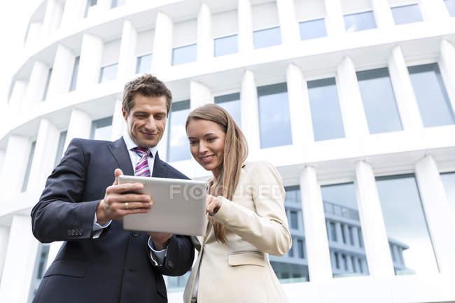 Homme d'affaires et femme d'affaires avec tablette devant l'hôtel — Photo de stock