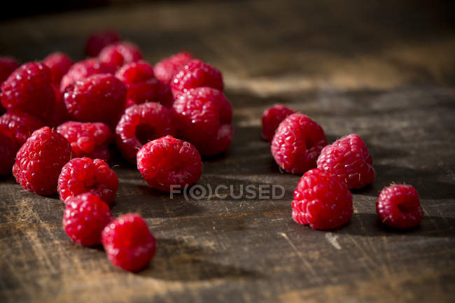 Fresh ripe Raspberries on brown wooden table — Stock Photo