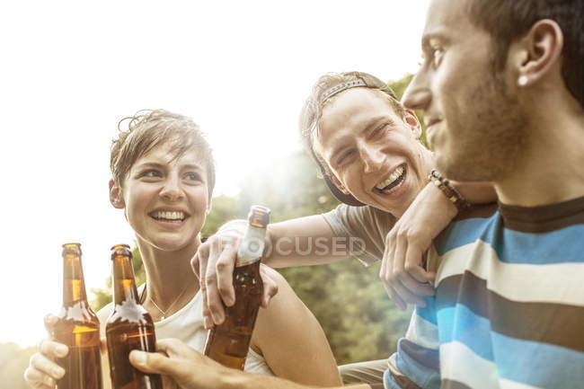 Três frinds relaxante com garrafas de cerveja — Fotografia de Stock