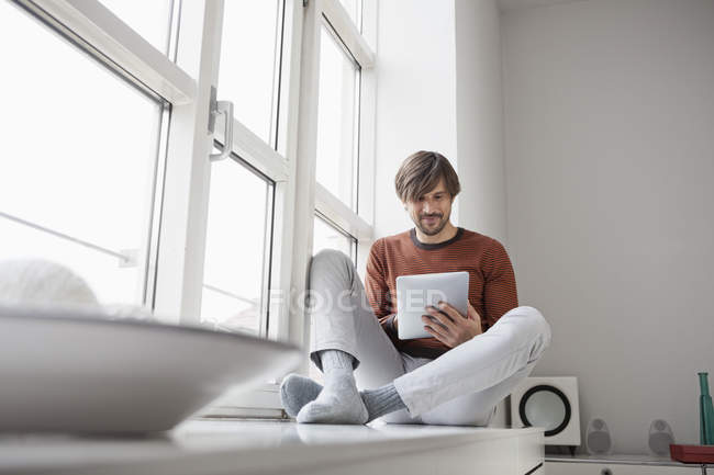 Людина за допомогою цифровий планшет і сидячи на підвіконні — стокове фото