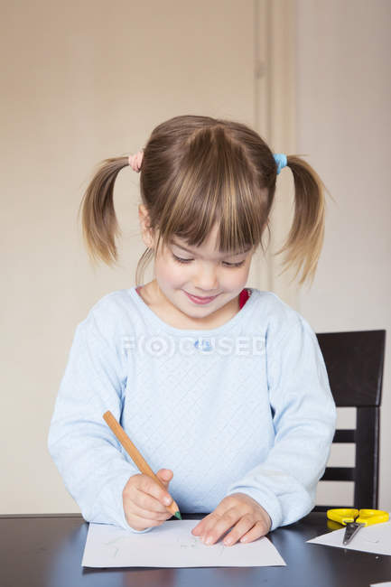 Portrait of little girl drawing with green crayon — Stock Photo
