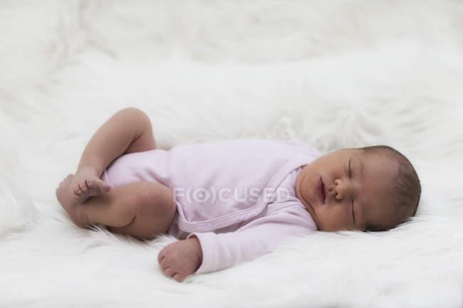 Спящая девушка новорожденного на белой ткани — стоковое фото