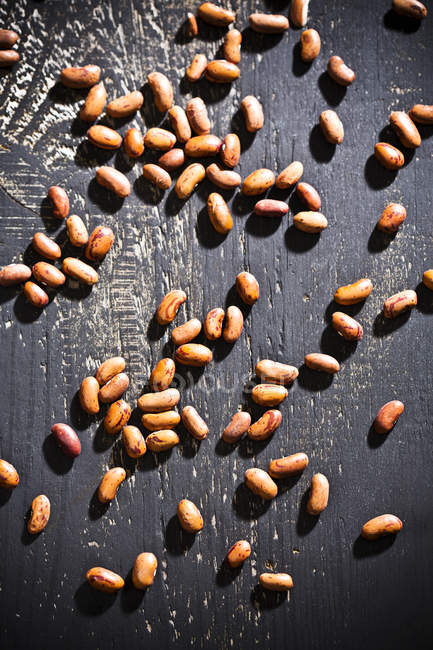 Quall beans on dark wood, elevated view — Stock Photo