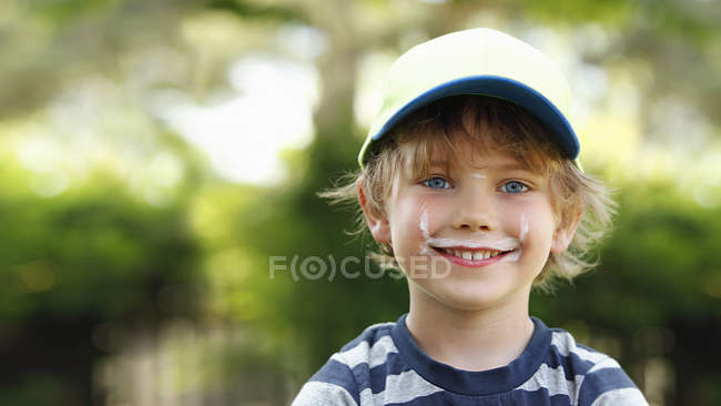 Portrait de petit garçon souriant avec moustache de lait — Photo de stock