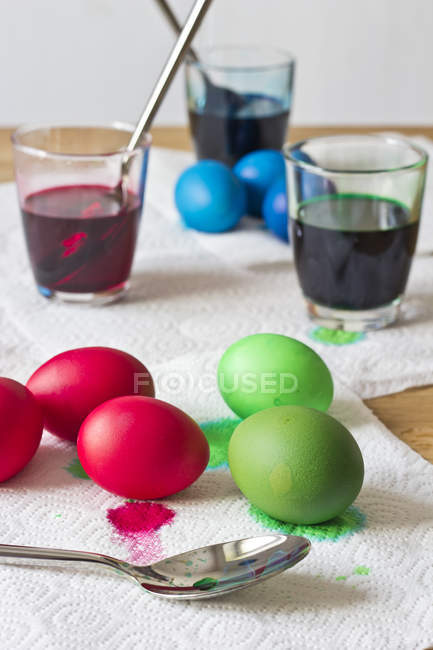 Dyeing Easter eggs on napkins with spoon — Stock Photo