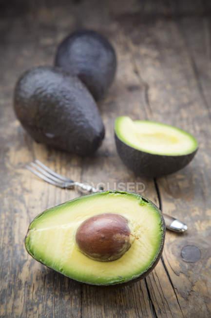 Halbierte und ganze Avocado auf dunklen Holztisch — Stockfoto