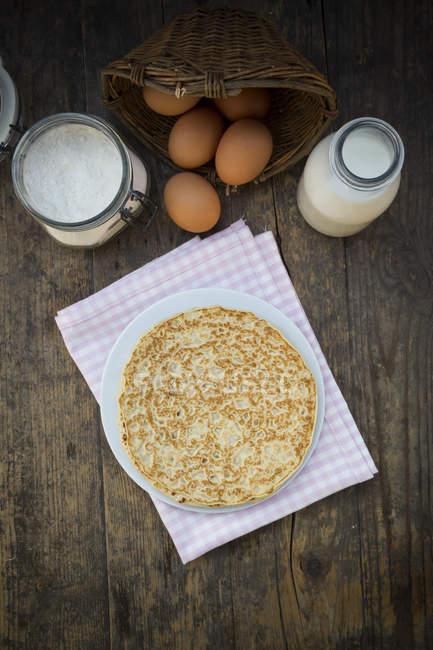 Pancake in frying pan and ingredients on dark wood — Stock Photo
