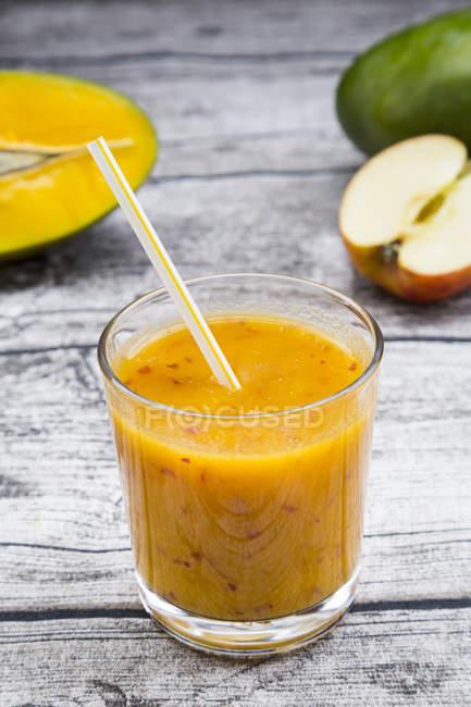 Gros plan sur verre de smoothie aux pommes à la mangue avec paille à boire sur table en bois gris — Photo de stock