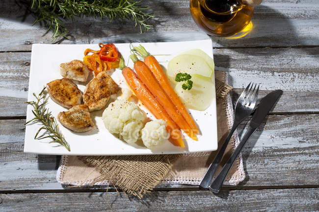 Primer plano de rodajas de filete de pollo con coliflor, zanahorias y pimiento morrón en el plato - foto de stock