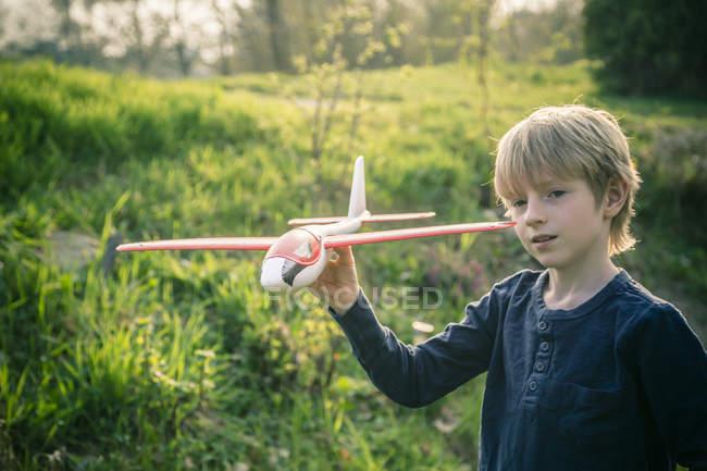 Chico jugando con juguete avión - foto de stock