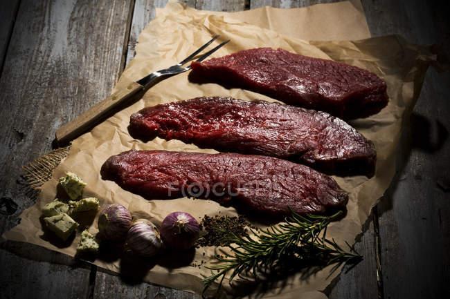 Стейки из говядины, чеснок, розмарин, масло с пряностями и перец на бумагу для выпечки — стоковое фото
