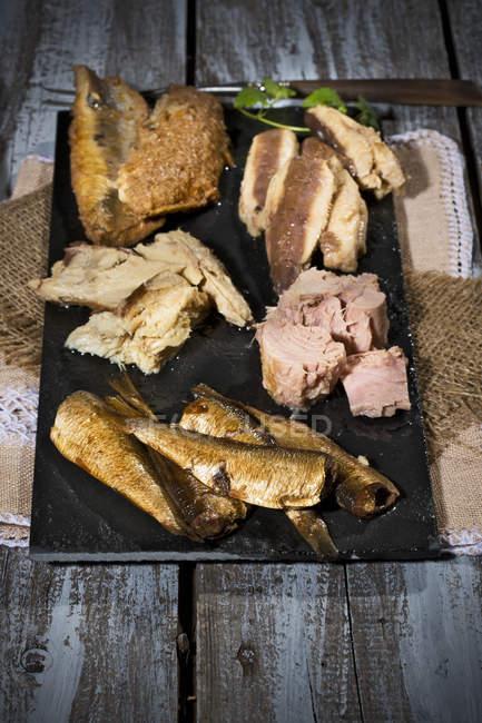 Varietà di pesce marinato e marinato su ardesia su legno shabby — Foto stock
