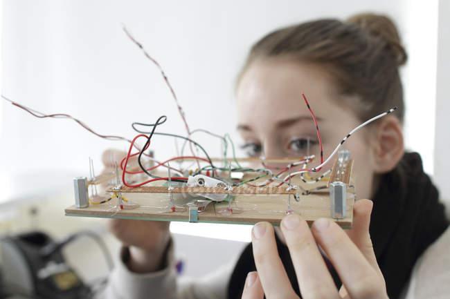 Jeune femme tenant un composant pour un capteur optique dans un atelier électronique — Photo de stock