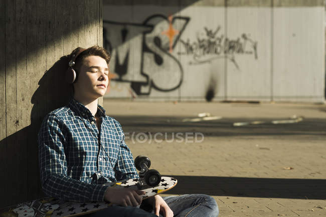 Teenager with skateboard hearing music — Stock Photo