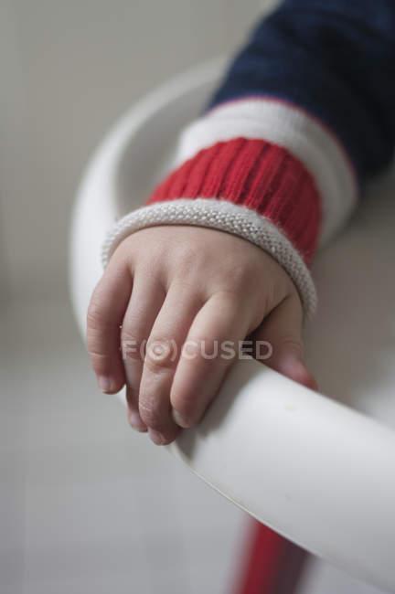 Рука малыша держит край детского стульчика — стоковое фото