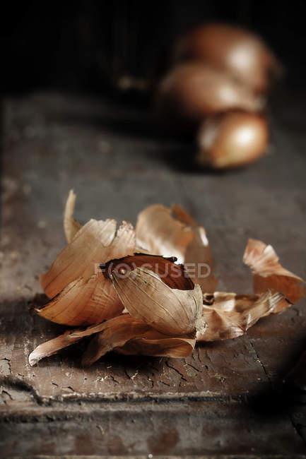 Cascas de cebola e cebola no fundo escuro de madeira — Fotografia de Stock