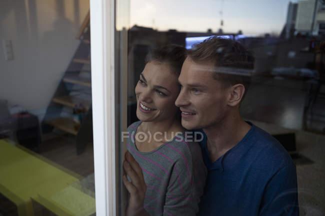 Lächelndes Paar hinter Fenster — Stockfoto