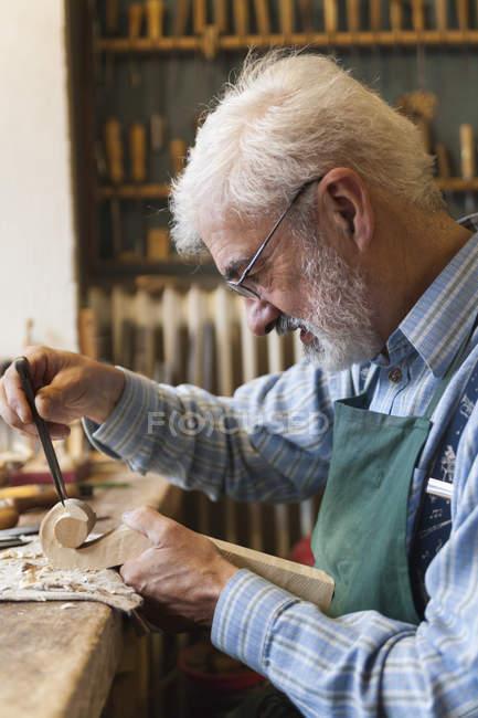 Violin maker at work carving wooden violin detail — Stock Photo