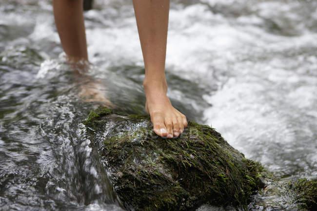 Frauenfüße überqueren Bach mit Fels — Stockfoto