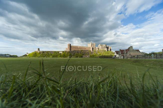 Reino Unido, Northumberland, Bamburgh, vista para o Castelo de Bamburgh em campo verde — Fotografia de Stock
