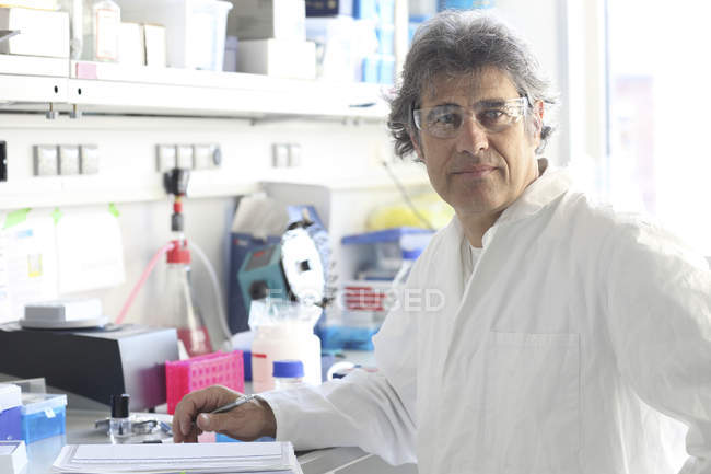 Scientist in laboratory journalizing rest results — Stock Photo