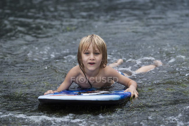 Young boy lying with swimming board on the waterfront — Stock Photo