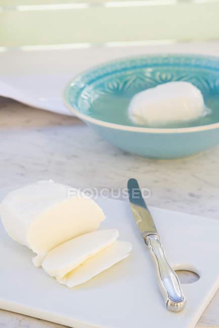 Чаша из сыра моцарелла, нарезанные моцарелла и нож на белый мрамор — стоковое фото