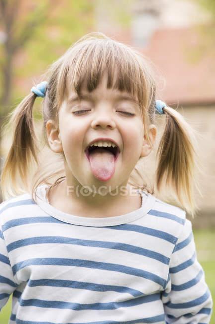 Porträt des kleinen Mädchens mit geschlossenen Augen und ausgestreckten Zunge — Stockfoto