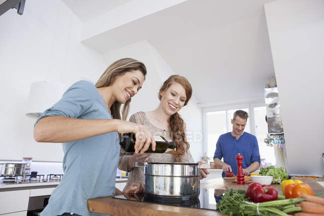 Three friends cooking together — Stock Photo
