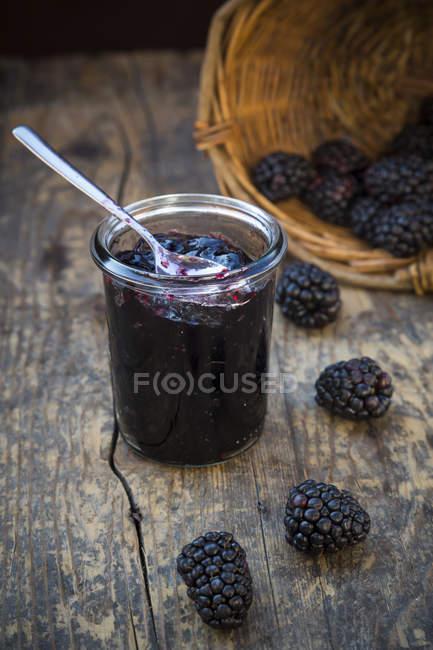 Close-up da cesta de amoras e preservando pote de geleia de blackberry com colher de madeira mesa — Fotografia de Stock