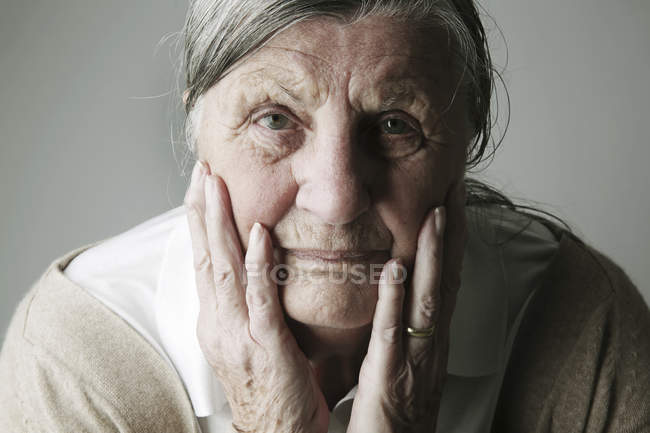 Portrait of senior woman with head in her hands — Stock Photo