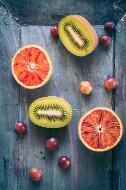 Виноград и половина крови оранжевый с киви на серой деревянной поверхности — стоковое фото