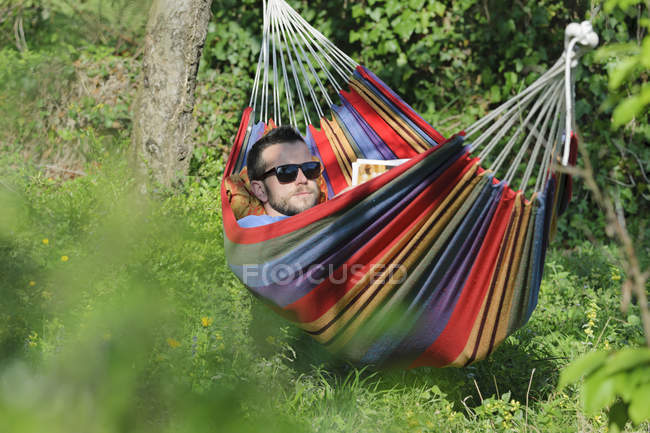 Young man lying in hammock and reading a magazine — Stock Photo
