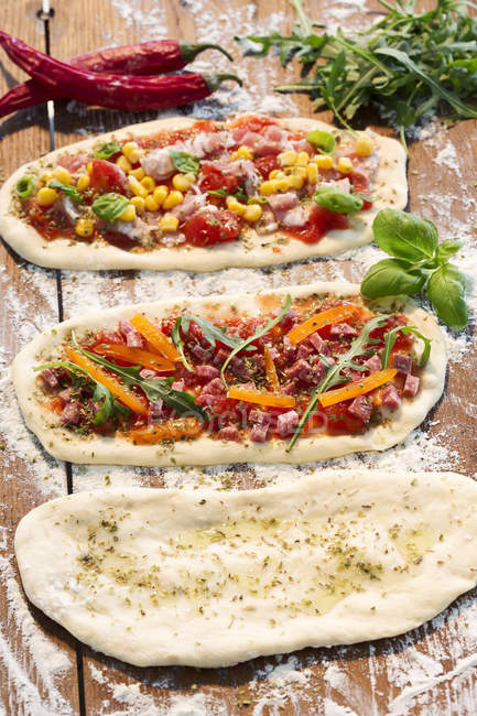Pâte à pizza crue, avec jambon, fromage, tomates, roquette, maïs, paprika, huile d'ail et basilic — Photo de stock