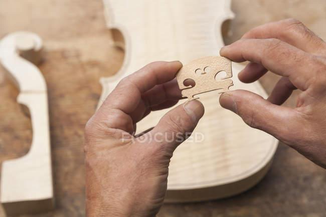 Violin maker hands holding carved wooden detail — Stock Photo