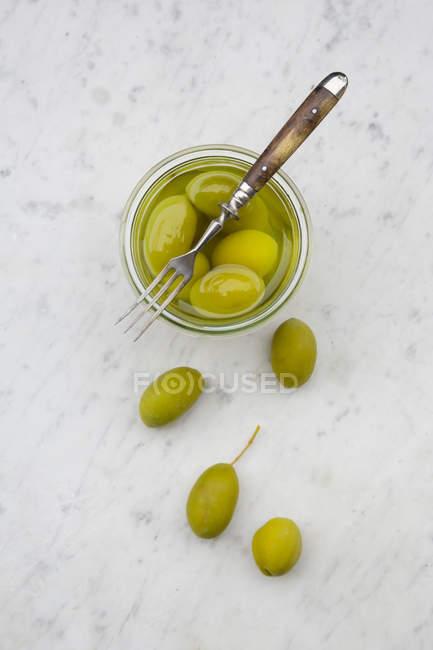 Preservando o pote de azeitonas verdes em conserva e um garfo em mármore branco, elevou a vista — Fotografia de Stock