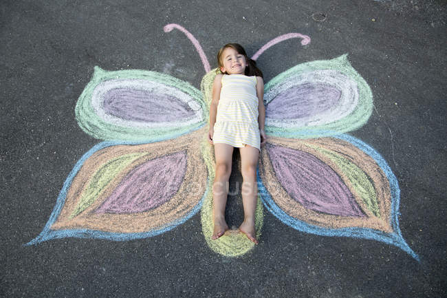 Little girl lying on street painting — Stock Photo