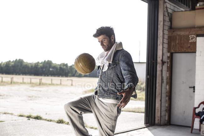 Stylish Man wearing denim jacket kicking football — Stock Photo