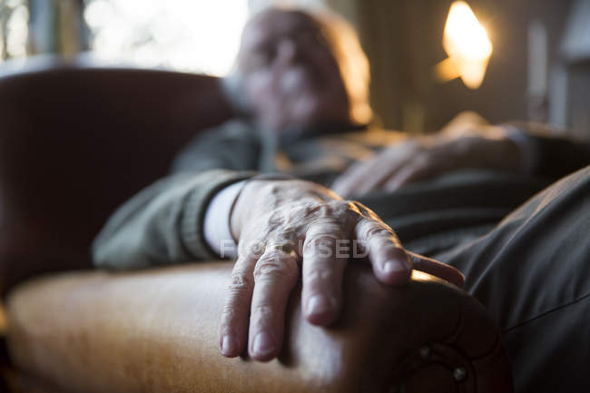 Senior man relaxing in armchair, closeup view of hand — Stock Photo