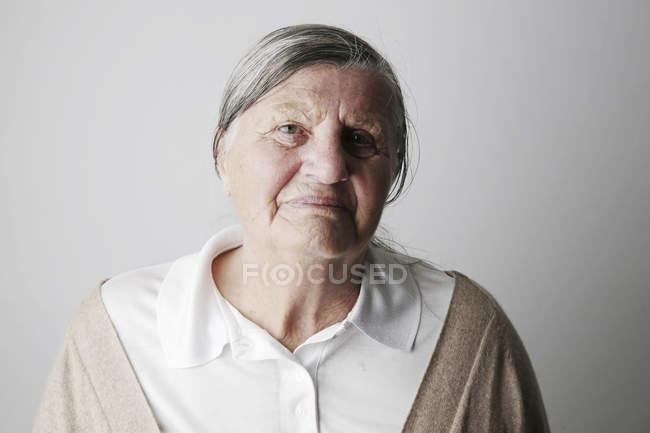 Retrato de mujer senior contra pared - foto de stock