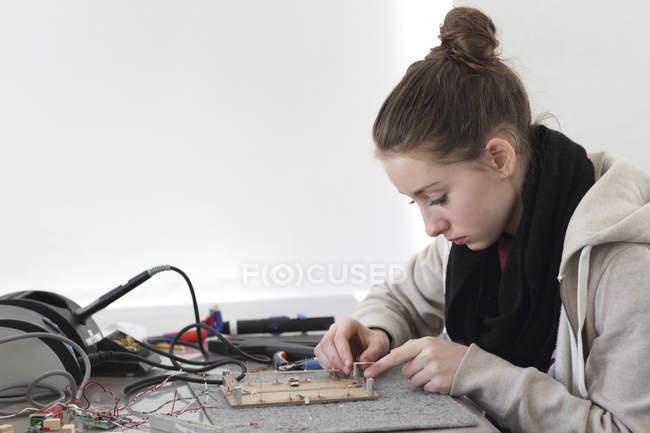 Jeune femme travaillant sur capteur optique dans un atelier électronique — Photo de stock