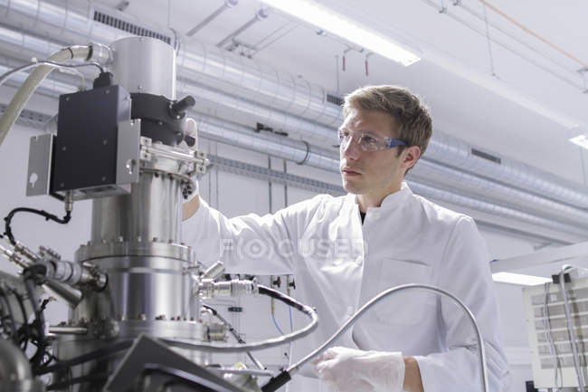Scientist standing in analytical laboratory with scanning electron microscope and spectrometer — Stock Photo