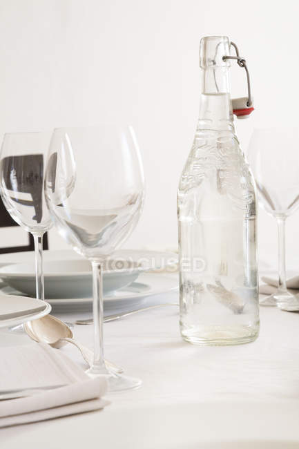 Festive laid table with wine glasses and bottle of water — Stock Photo