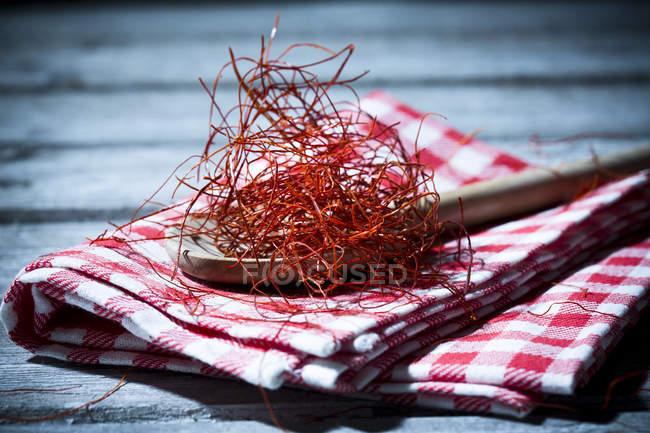Дерев'яною ложкою з Чилі ниток на кухонне рушник і дерев'яний стіл — стокове фото