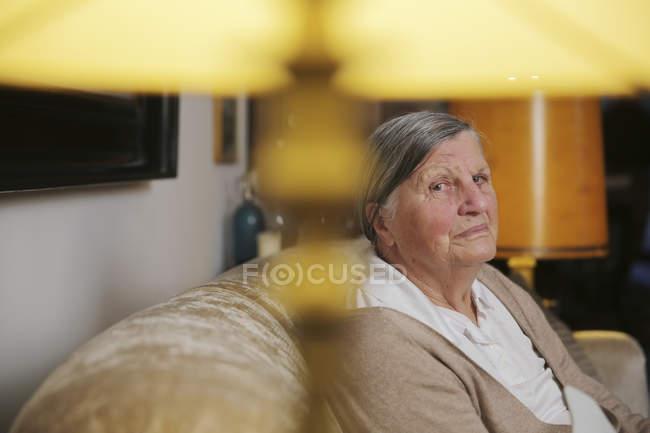 Старший жінка, сидячи на дивані у вітальні — стокове фото