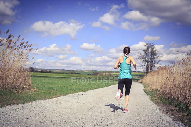 Жінка біг через сільської місцевості — стокове фото